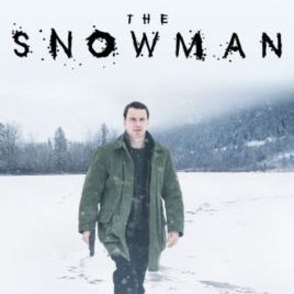 The Snowman, with lead actor Michael Fassbender walking in the snow holding a fun