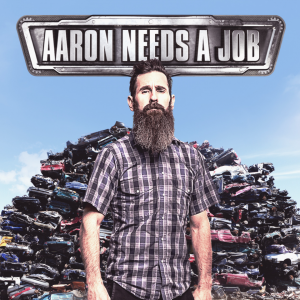 Aaron Needs a Job - A man with a long beard stands in front of a junkpile of cars,
