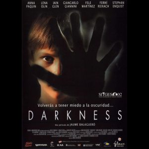 A poster for Darkness, with a shadowy hand in front of a face