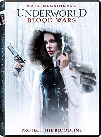 Kate Beckinsale standing in winter wooded area, two guns in hand.